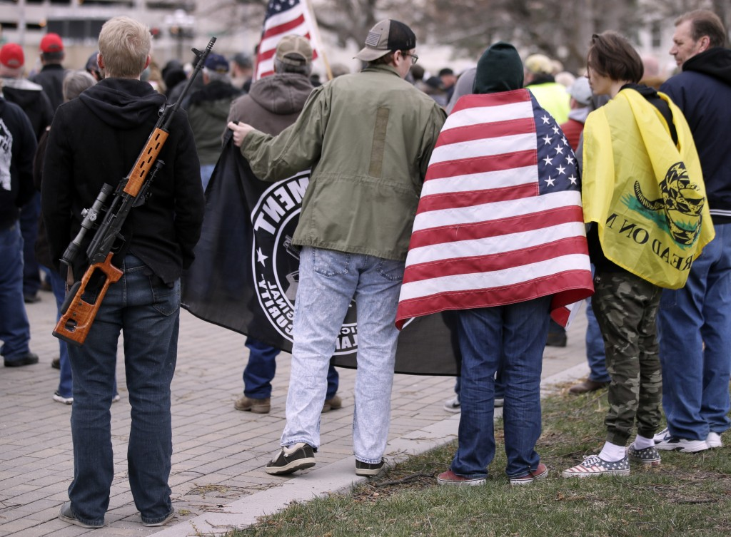 Pro-gun supporters wrapped in flags and carrying guns rally at the Kansas Statehouse in Topeka, Kan., Saturday, April 14, 2018. The rallies come less