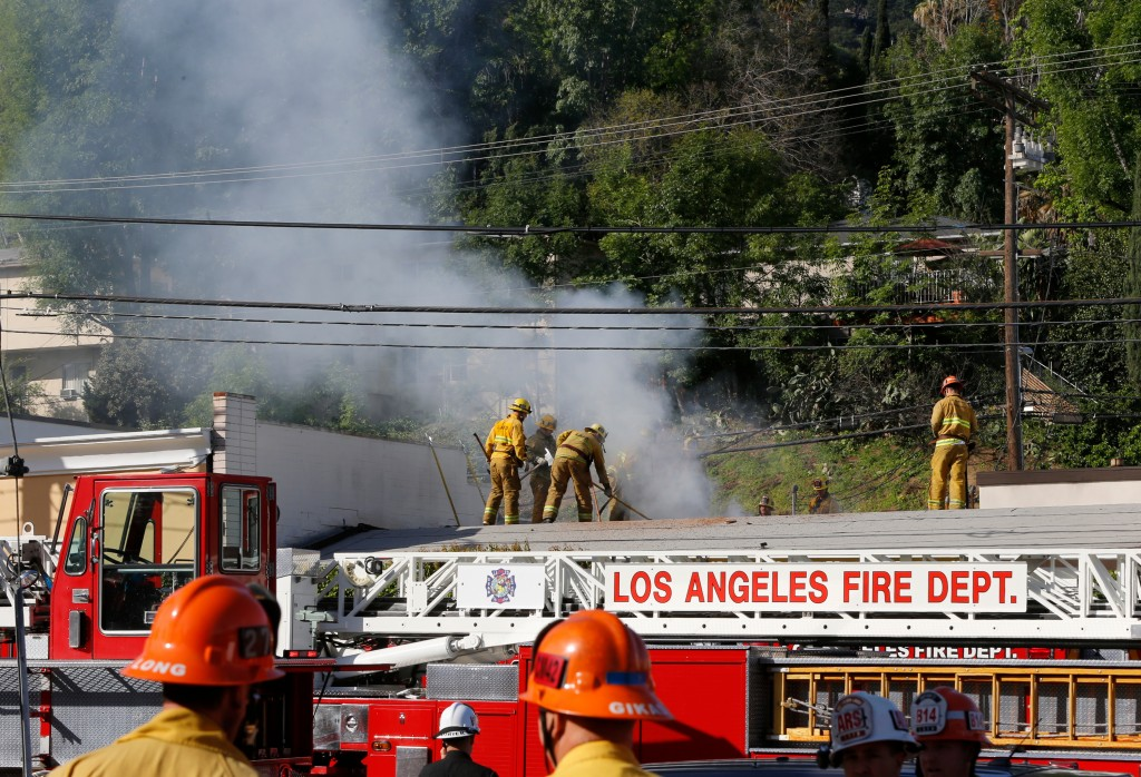 Los Angeles firefighters knock down hot spots on the roof of a music studio in Los Angeles Saturday, April. 14, 2018. Officials says two people were k