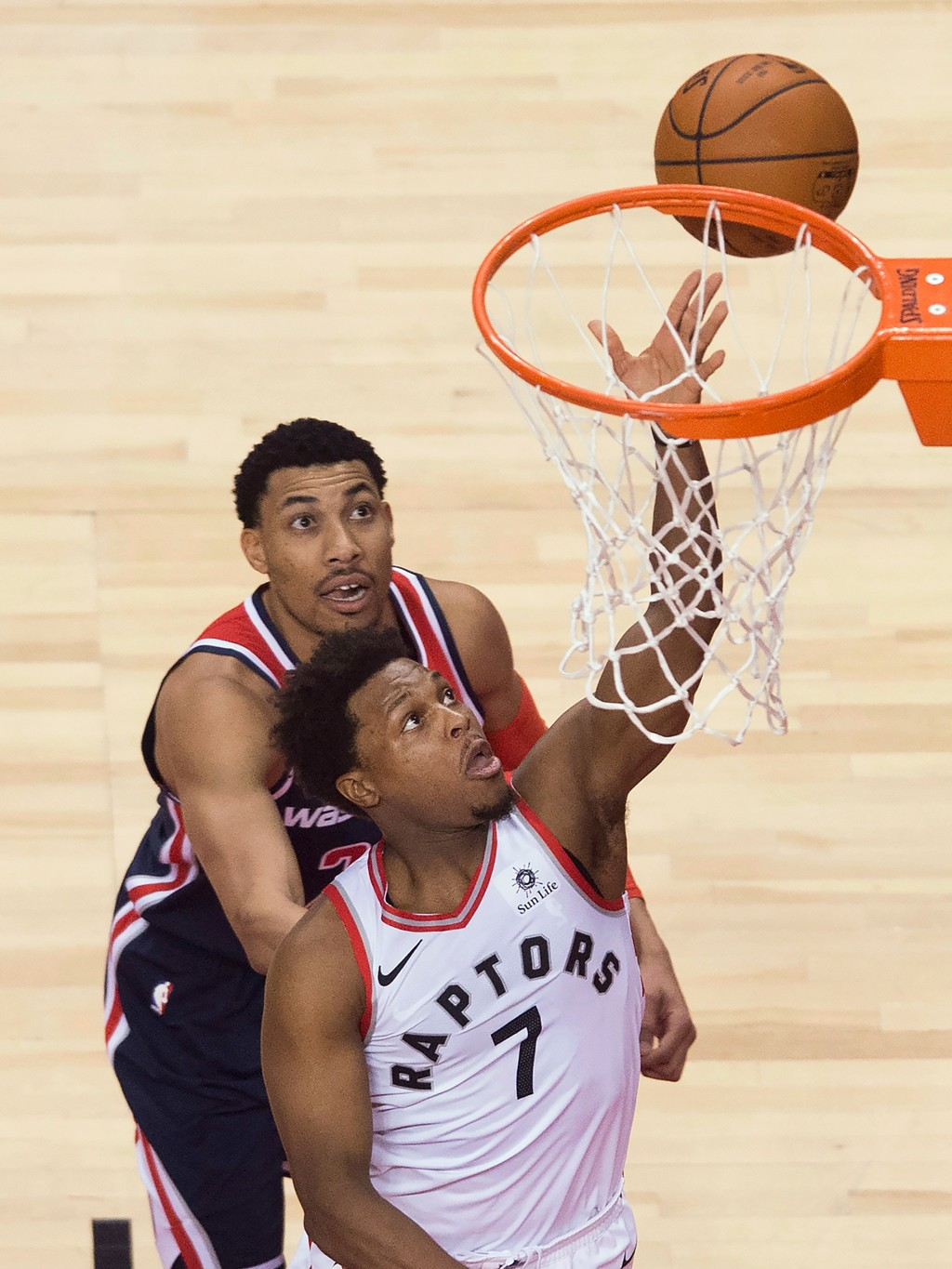 Toronto Raptors guard Kyle Lowry (7) scores past Washington Wizards forward Otto Porter Jr. (22) during the second half of Game 1 of an NBA basketball