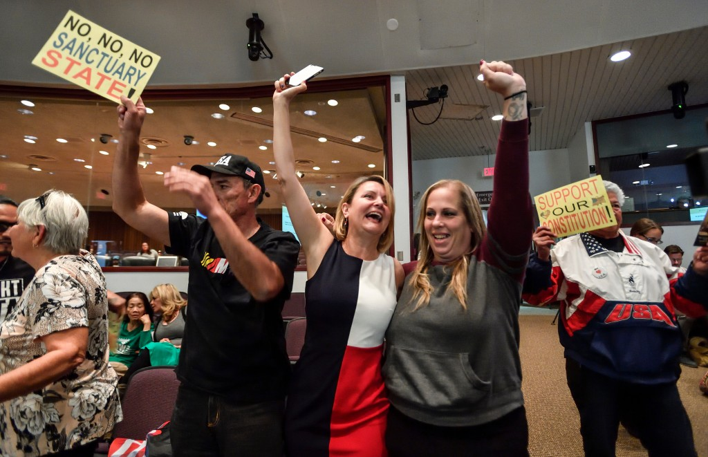 FILE - In this March 27, 2018, file photo, David Hernandez, left, Genevieve Peters, center, and Jennifer Martinez celebrate after the Orange County Bo
