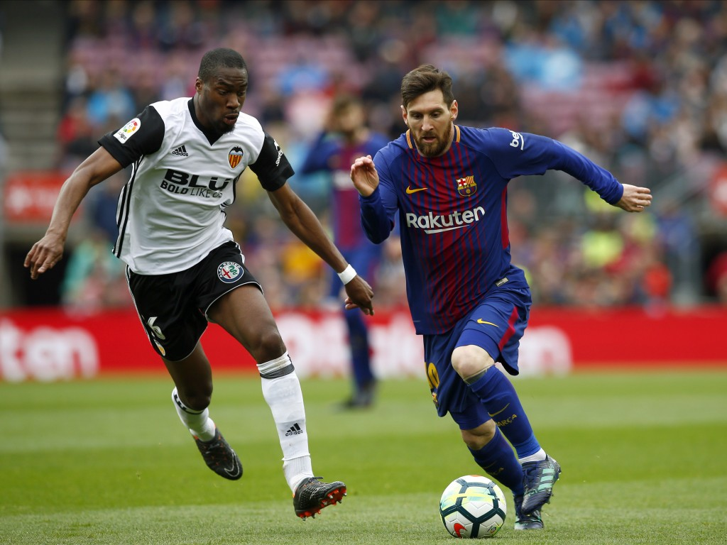 FC Barcelona's Lionel Messi, right, duels for the ball against Valencia's Geoffrey Kondogbia during the Spanish La Liga soccer match between FC Barcel