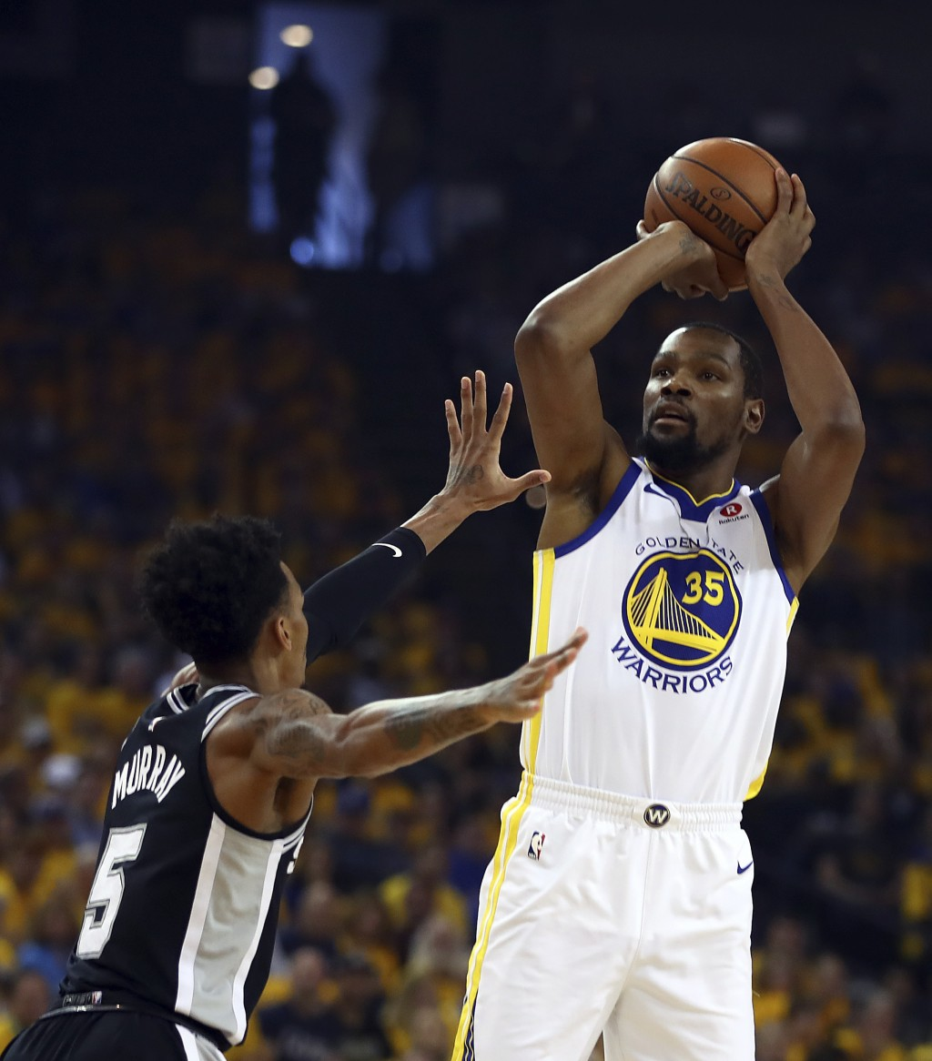 Golden State Warriors' Kevin Durant, right, shoots against San Antonio Spurs' Dejounte Murray (5) during the first half in Game 1 of a first-round NBA