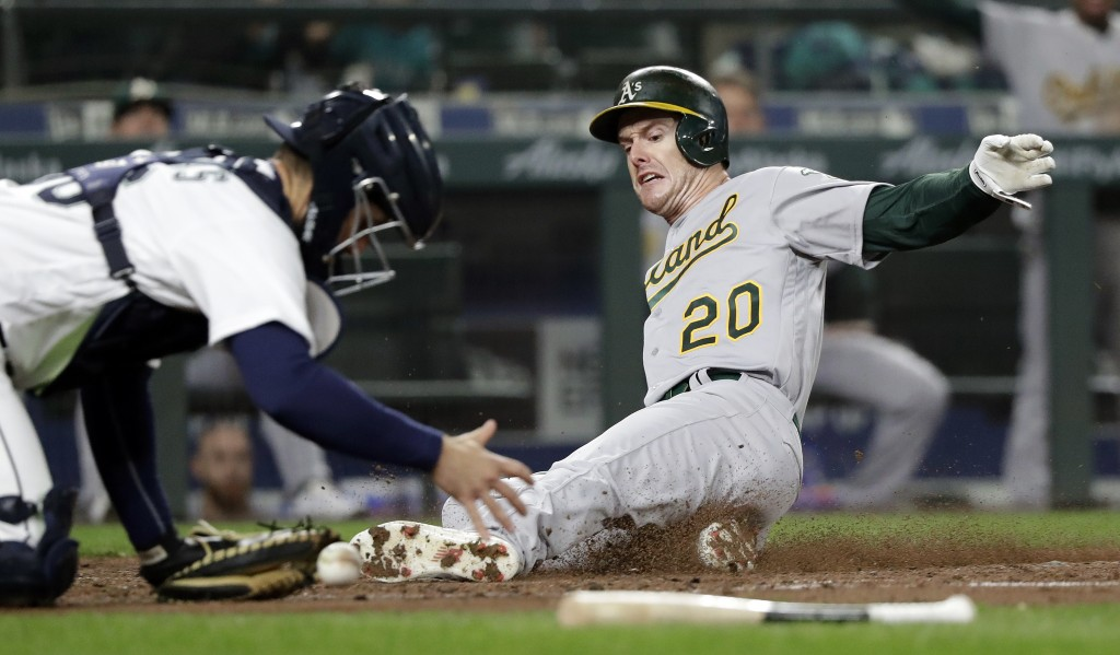Oakland Athletics' Mark Canha (20) slides safely into home as Seattle Mariners catcher David Freitas tries to get a grip on the ball during the third