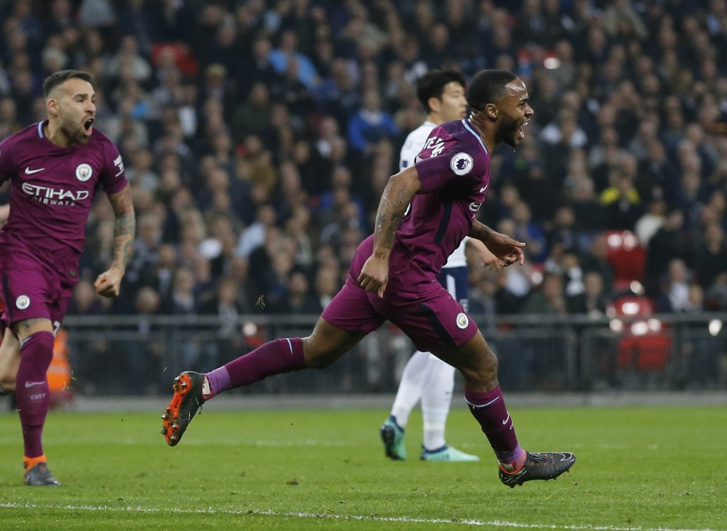 Manchester City's Raheem Sterling, right, celebrates with team mates after scoring his sides third goal during the English Premier League soccer match
