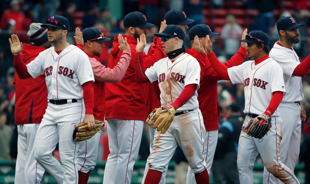Boston Red Sox players, from left foreground, Andrew Benintendi, Brock Holt and Tzu-Wei Lin celebrate after defeating the Baltimore Orioles in a baseb