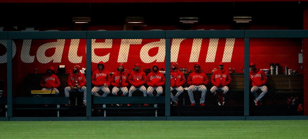 Los Angeles Angels pitchers sit under heat lamps in the bullpen as temperatures drop into the 30s during the fifth inning of a baseball game against t