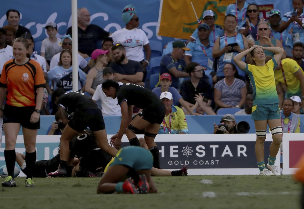 New Zealand players celebrate after defeating Australia in extra time to win their rugby sevens gold medal match at Robina Stadium during the 2018 Com