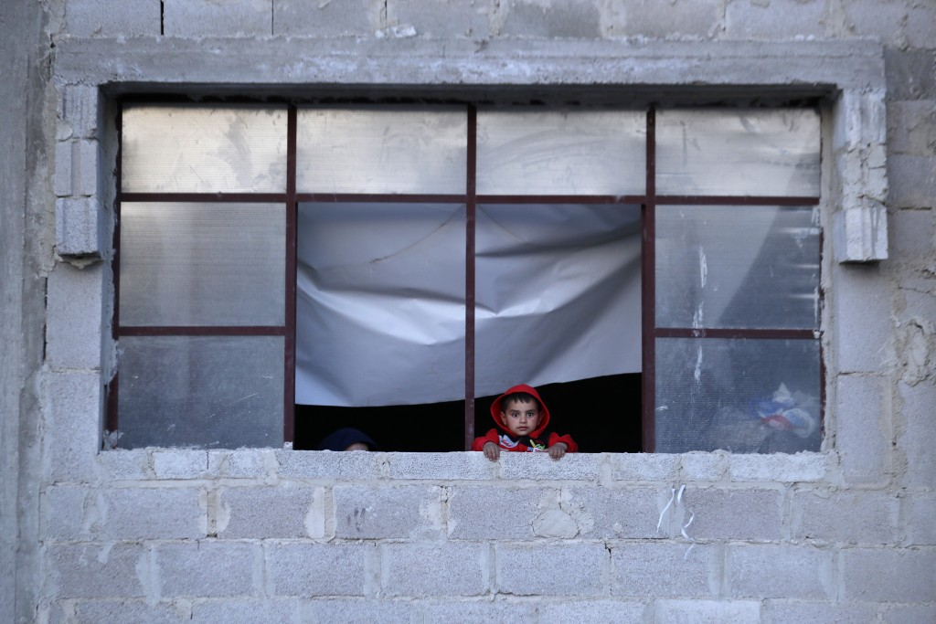In this Friday, April 13, 2018 photo, a Syrian child who was displaced with his family from eastern Ghouta watches from the window of his family's she