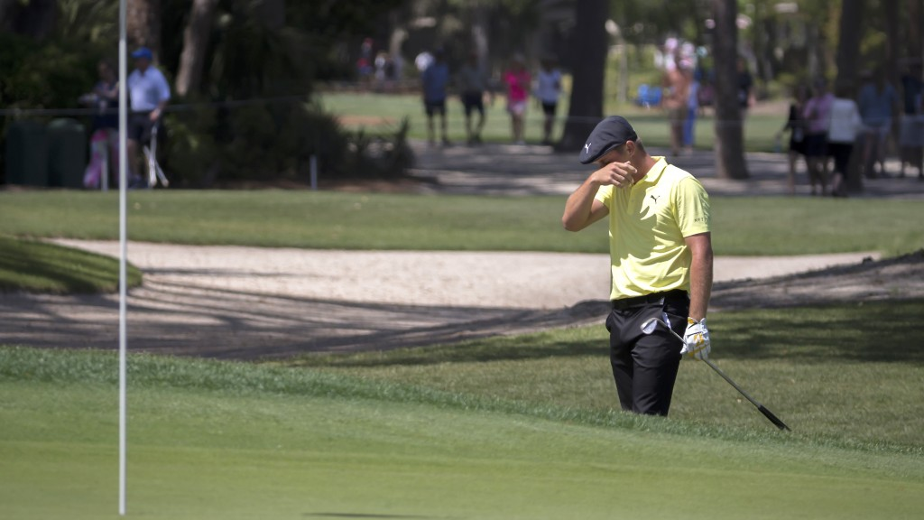 Bryson DeChambeau reacts after hitting his shot out into the bunker on the second green from the rough during the third round of the RBC Heritage golf