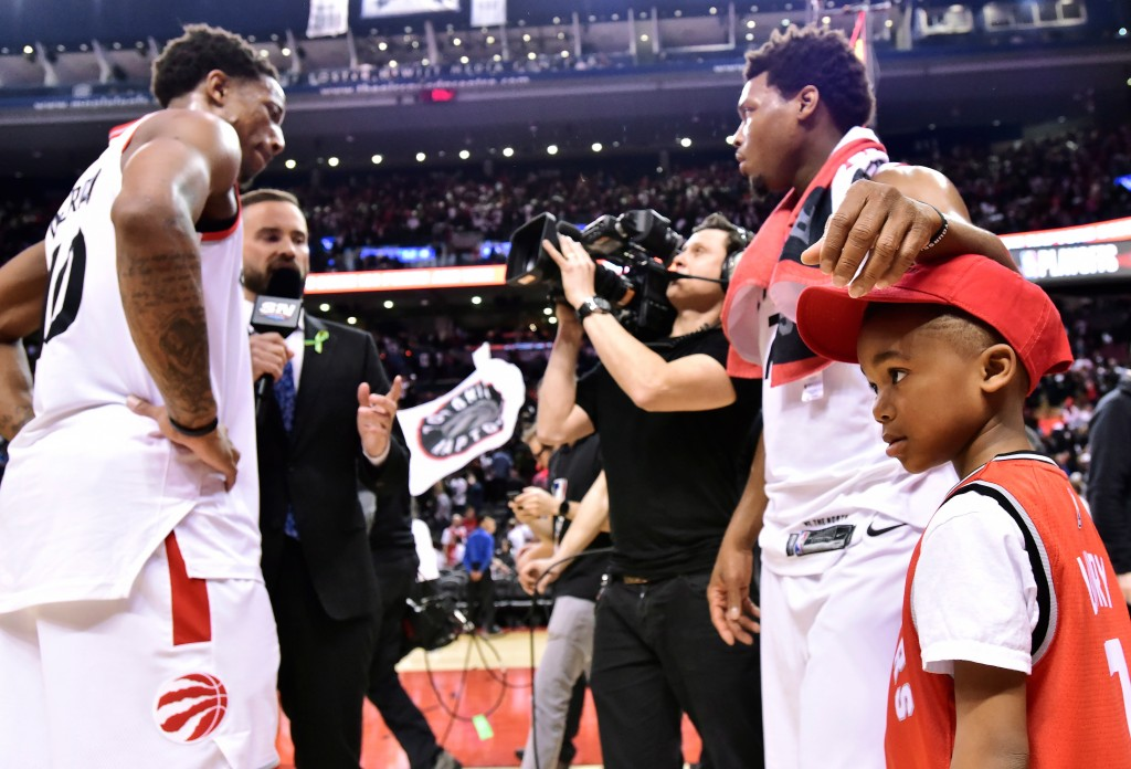 Toronto Raptors guard Kyle Lowry, top right, celebrates with his son Karter and teammate DeMar DeRozan after the Raptors defeated the Washington Wizar