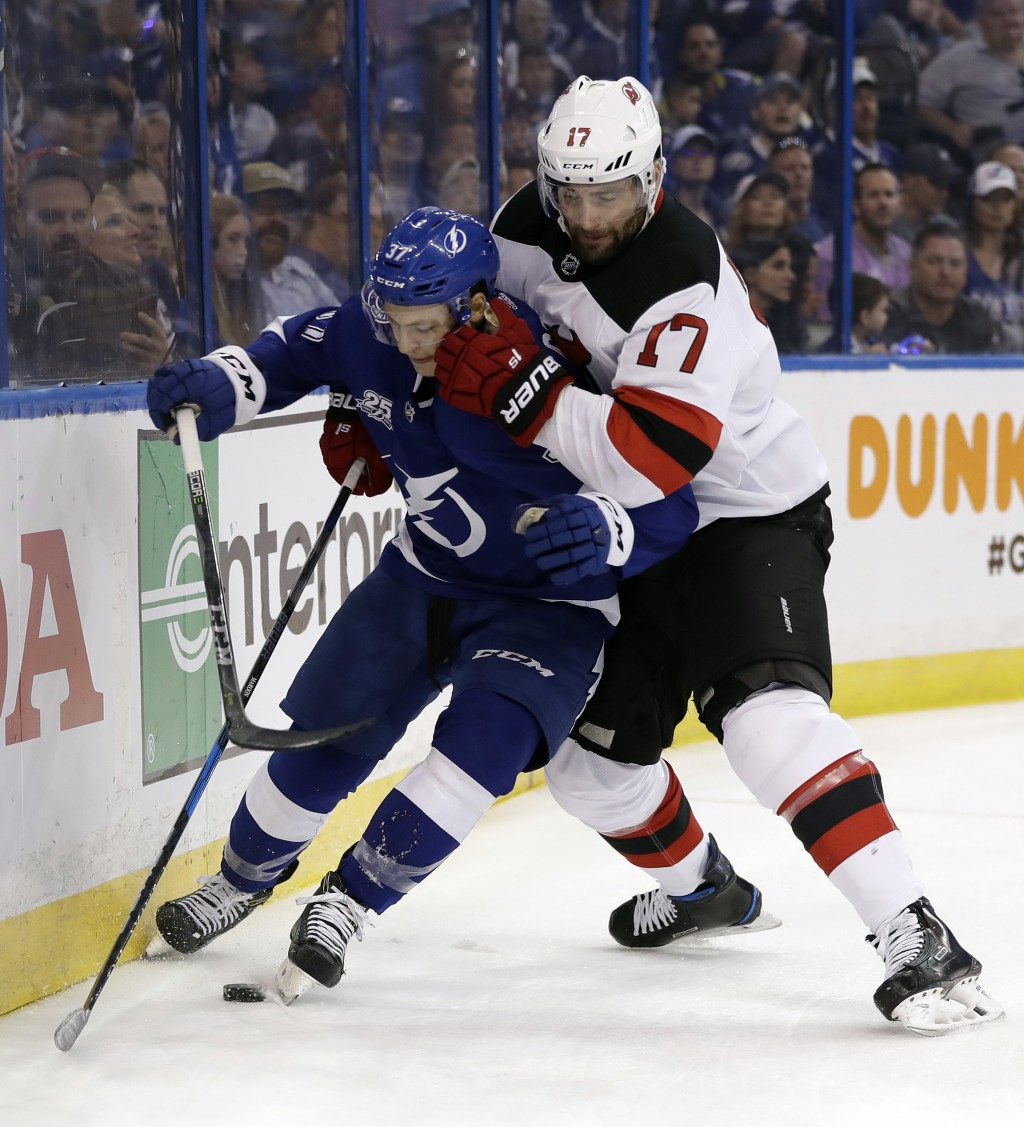 New Jersey Devils left wing Patrick Maroon (17) forces Tampa Bay Lightning center Yanni Gourde into the dasher during the first period of Game 2 of an