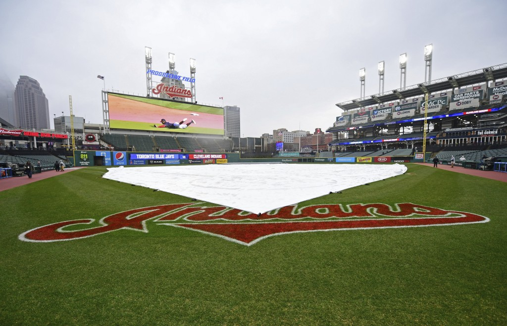 A tarp covers the field during a rain delay of a baseball game between the Toronto Blue Jays and Cleveland Indians, Saturday, April 14, 2018, in Cleve...