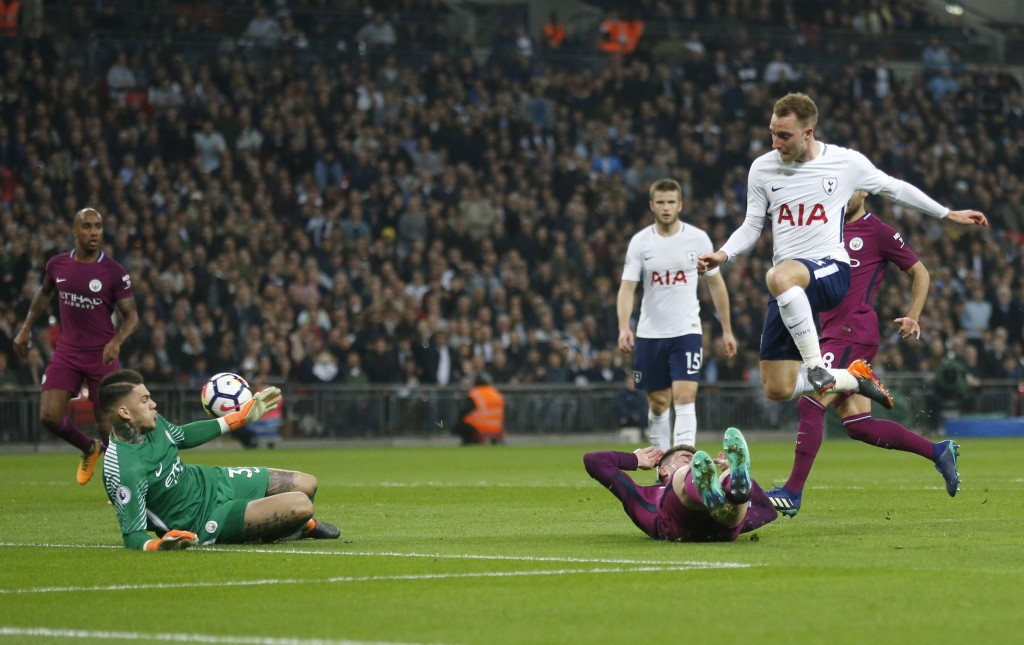 Tottenham's Christian Eriksen, right, scores during the English Premier League soccer match between Tottenham Hotspur and Manchester City at Wembley s