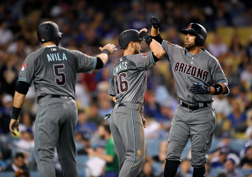 Arizona Diamondbacks' Deven Marrero, right, is congratulated by Alex Avila, left, and Chris Owings after hitting a three-run home run during the fourt