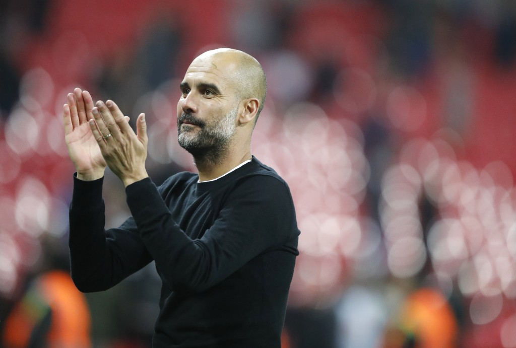 Manchester City manager Pep Guardiola applauds the fans as he walks from the pitch after the end of the English Premier League soccer match between To...