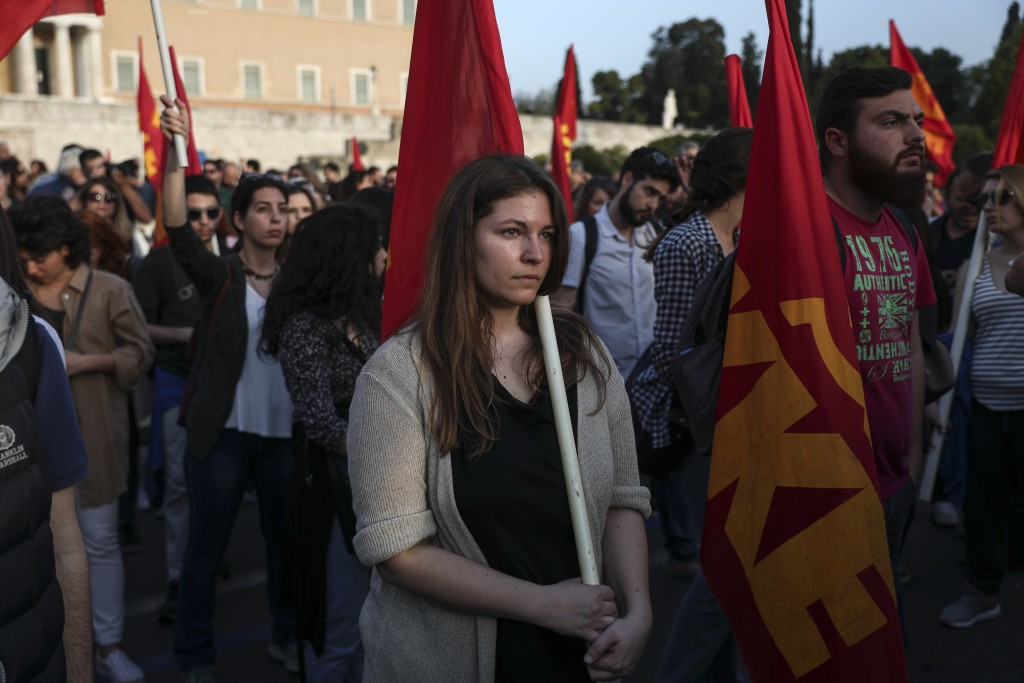 Supporters of the Greek Communist party take part in an anti-war rally in front of the parliament, in Athens, Saturday, April 14, 2018. Thousands of s