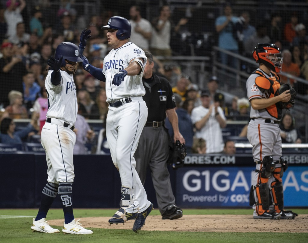 San Diego Padres' Hunter Renfroe, center, celebrates his two-run home run with Freddy Galvis, left, as San Francisco Giants catcher Nick Hundley stand