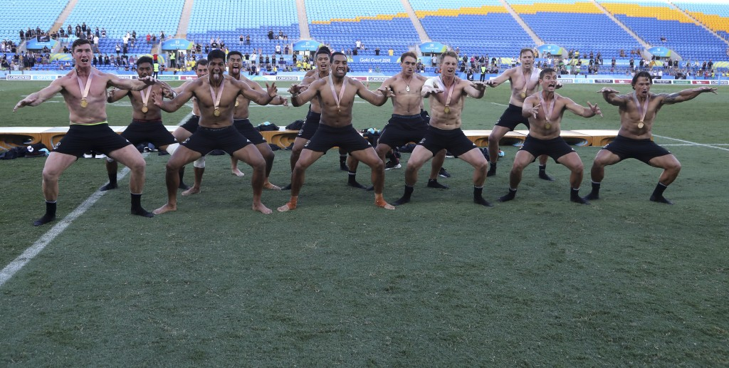 The New Zealand men's rugby sevens team perform a haka as they celebrate after defeating Fiji to win the gold medal match at Robina Stadium during the