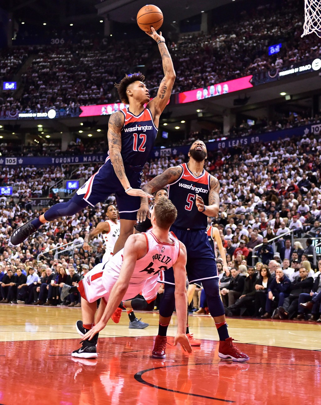 Washington Wizards forward Kelly Oubre Jr. (12) shoots over Toronto Raptors centrt Jakob Poeltl (42) as Wizards forward Markieff Morris (5) watches du