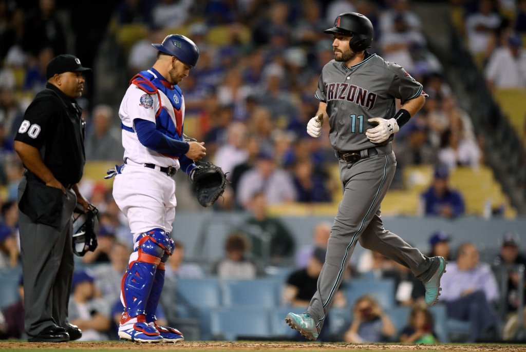 Arizona Diamondbacks' A.J. Pollock, right, scores after hitting a two-run home run as Los Angeles Dodgers catcher Yasmani Grandal, center, and home pl