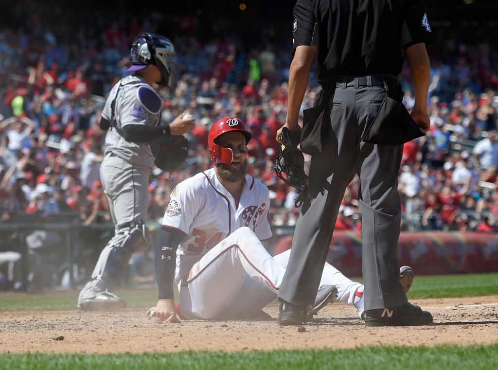 Washington Nationals' Bryce Harper (34) sits on the dirt after he slid home during the sixth inning of a baseball game against the Colorado Rockies Sa...