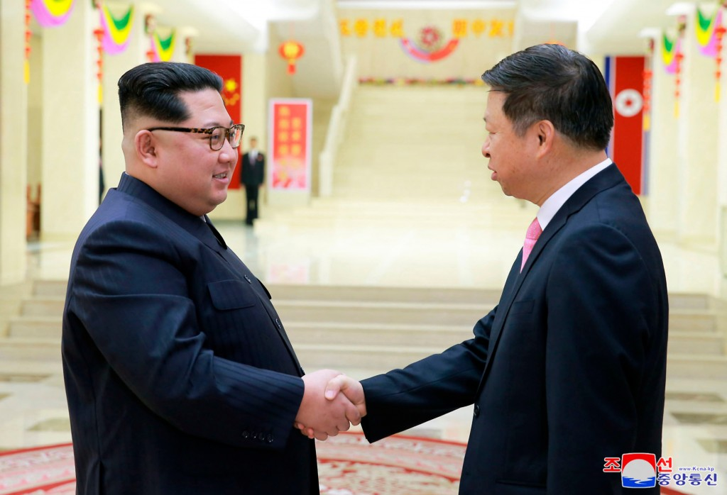 In this April 14, 2018, photo provided Sunday, April 15, 2018, by the North Korean government, North Korean leader Kim Jong Un, left, shakes hands wit