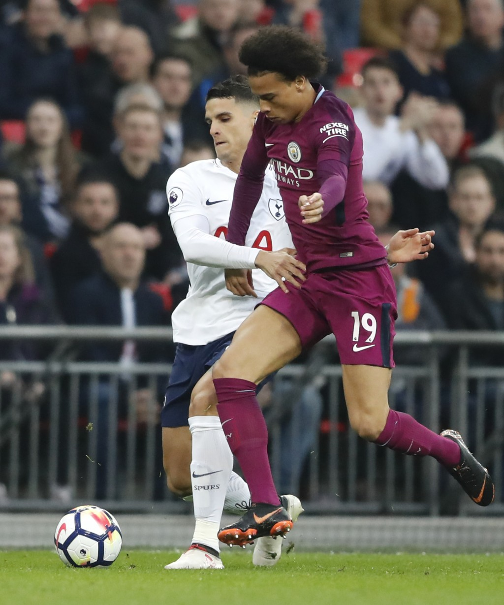 Tottenham's Erik Lamela, left, battles for the ball with Manchester City's Leroy Sane during the English Premier League soccer match between Tottenham