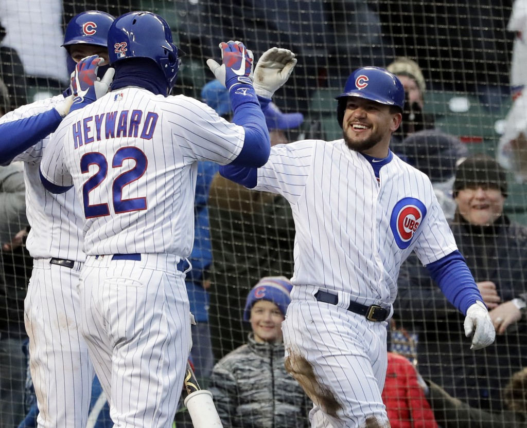 Chicago Cubs' Kyle Schwarber, right, celebrates with Jason Heyward (22) after they scoring on a wild pitch by Atlanta Braves relief pitcher Peter Moyl