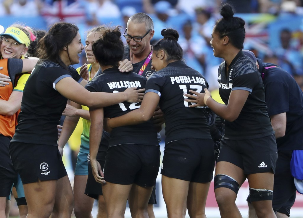 New Zealand players celebrate after defeating Australia in extra time in their women's rugby sevens gold medal match at Robina Stadium during the 2018