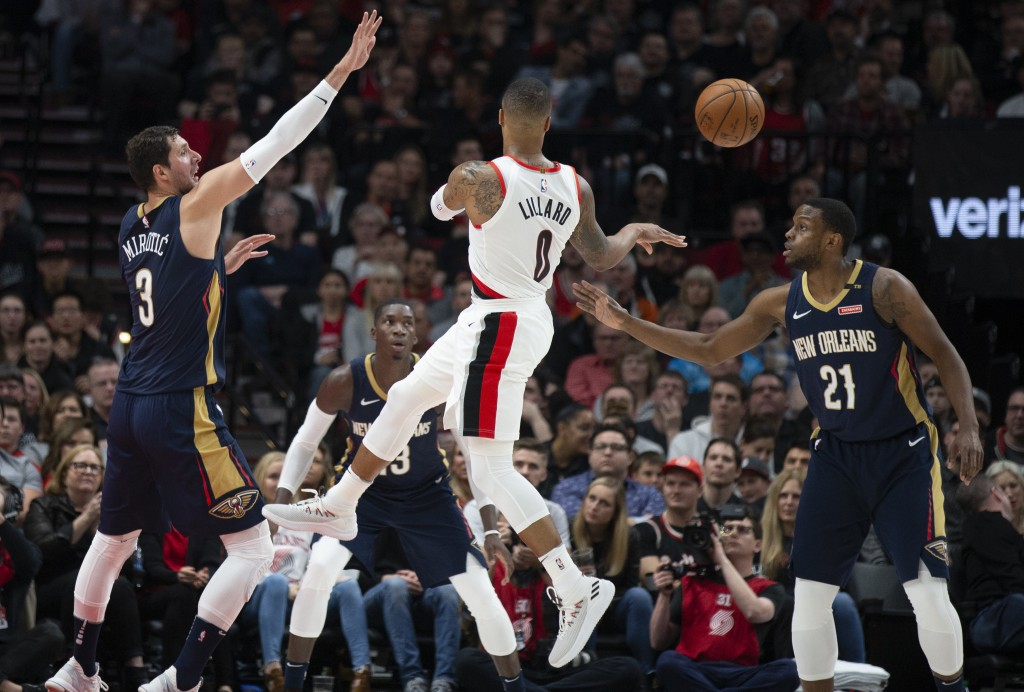 Portland Trail Blazers guard Damian Lillard passes against the defense of New Orleans Pelicans forward Nikola Mirotic, left, and forward Darius Miller