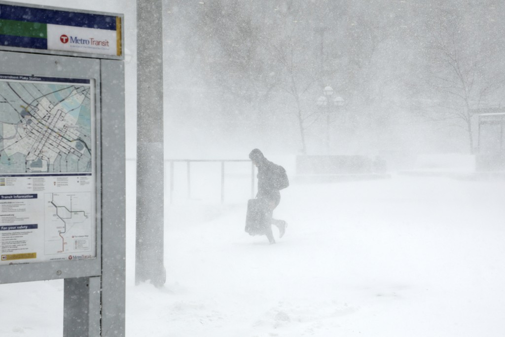 A traveler walks through the snow and ice to get to the Metro Government Center Plaza station as the snow picked up in downtown Minneapolis, Saturday,