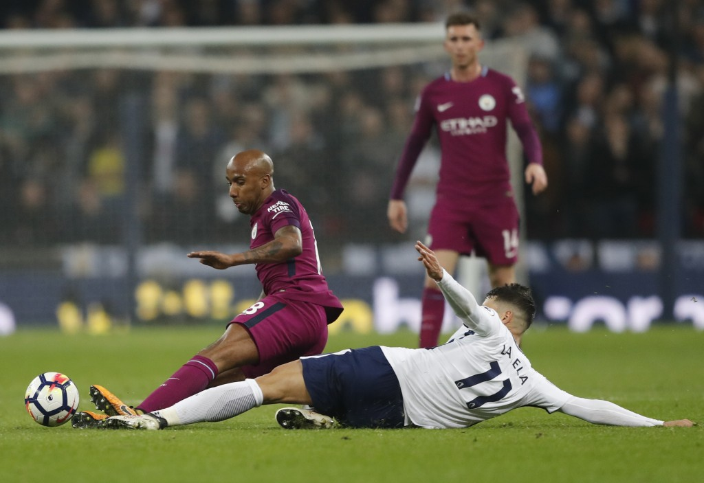 Manchester City's Fabian Delph, let, battles for the ball with Tottenham's Erik Lamela during the English Premier League soccer match between Tottenha
