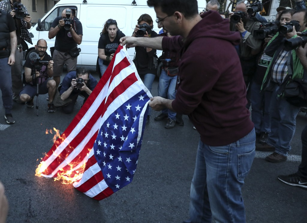 A protester holds a burning U.S. flag during a rally outside the U.S. embassy in Athens, Saturday, April 14, 2018. Thousands of supporters of the Gree
