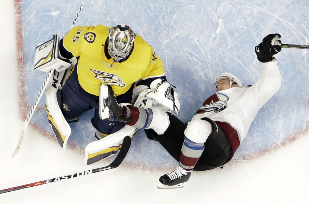 Colorado Avalanche defenseman Tyson Barrie (4) falls over Nashville Predators goalie Pekka Rinne (35), of Finland, during the second period in Game 2