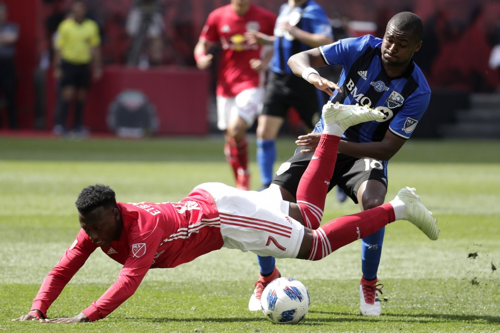 New York Red Bulls midfielder Derrick Etienne, bottom, is tripped up by Montreal Impact defender Chris Duvall during the second half of an MLS soccer