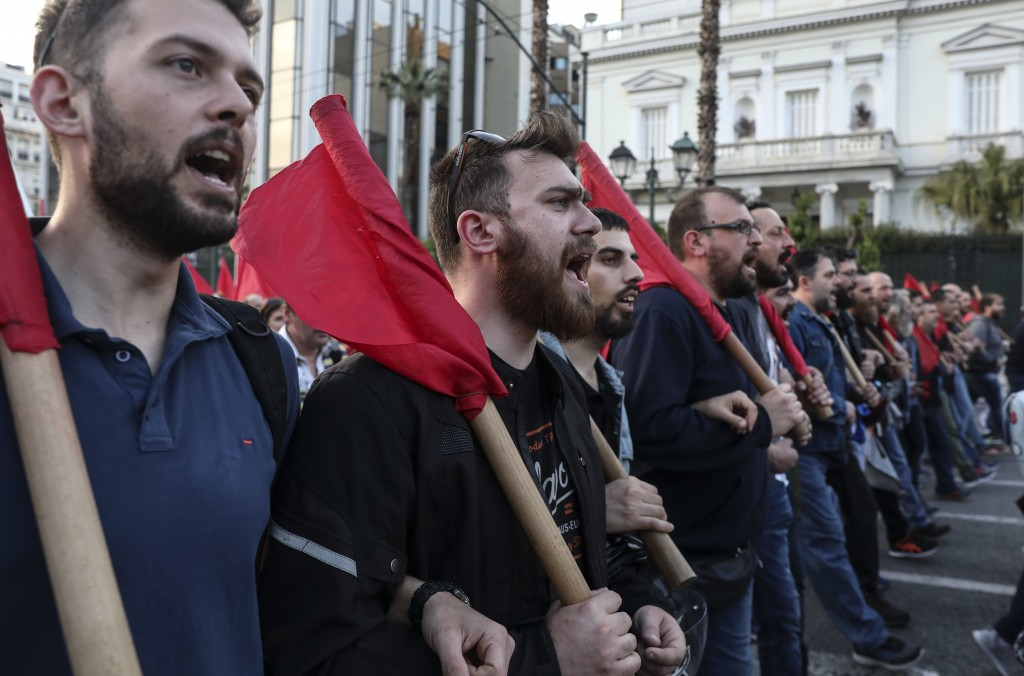 Supporters of the Greek Communist party chant slogans during an anti-war rally in Athens, Saturday, April 14, 2018. Thousands of supporters of the par