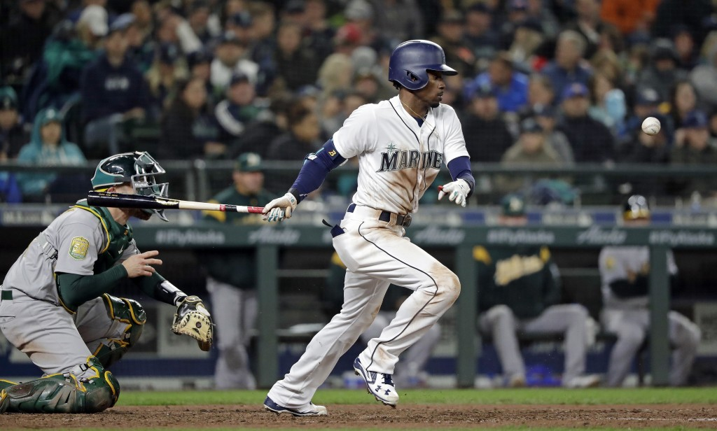 Seattle Mariners' Dee Gordon, right, singles in a run as Oakland Athletics catcher Jonathan Lucroy watches during the fifth inning of a baseball game ...
