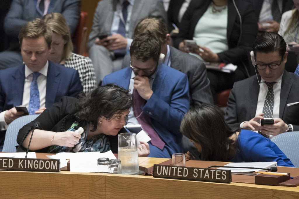 British Ambassador to the United Nations Karen Pierce, left and U.S. Ambassador to the United Nations Nikki Haley share a note during a Security Counc...