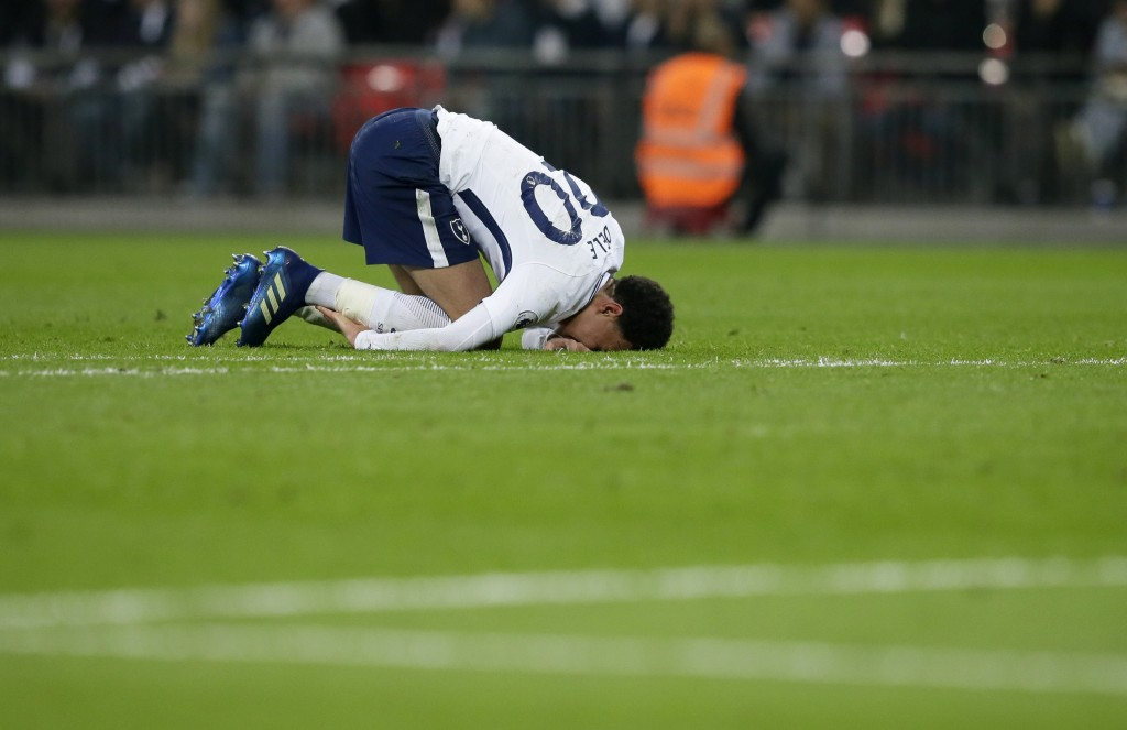 Tottenham's Dele Alli grimaces following a clash during the English Premier League soccer match between Tottenham Hotspur and Manchester City at Wembl
