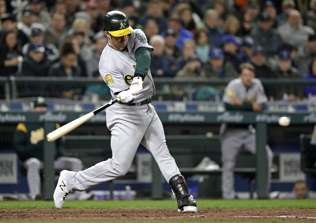 Oakland Athletics' Mark Canha singles in a pair of runs against the Seattle Mariners during the third inning during a baseball game Saturday, April 14...