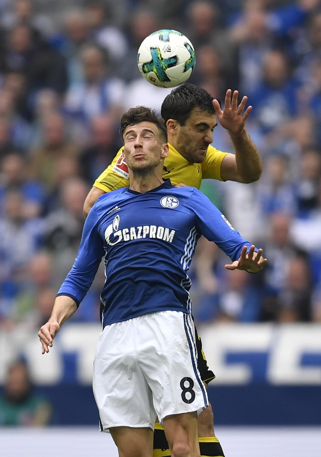 Schalke's Leon Goretzka and Dortmund's Sokratis challenge for the ball during the German Bundesliga soccer match between FC Schalke 04 and Borussia Do