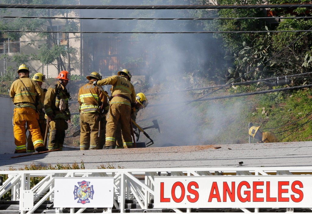 Los Angeles firefighrers knock down hot spots on the roof of a music studio in Los Angeles Saturday, April 14, 2018. Officials says two people were ki