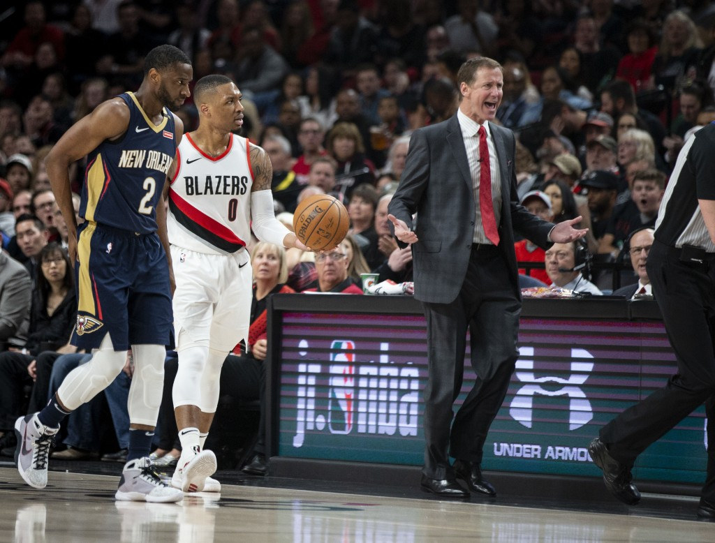 As New Orleans Pelicans guard Ian Clark and Portland Trail Blazers guard Damian Lillard listen, Blazers coach Terry Stotts questions an official durin