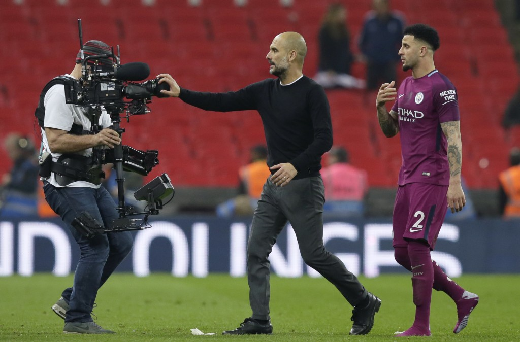 Manchester City coach Pep Guardiola covers a video camera with his hand as he leaves the field with Manchester City's Kyle Walker, right, at the end o