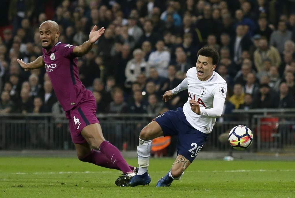 Manchester City's Vincent Kompany, left, steps on the foot of Tottenham's Dele Alli during the English Premier League soccer match between Tottenham H