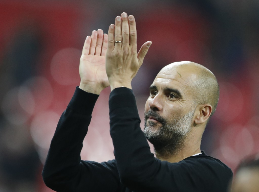 Manchester City manager Pep Guardiola applauds the fans as he walks from the pitch after the end of the English Premier League soccer match between To