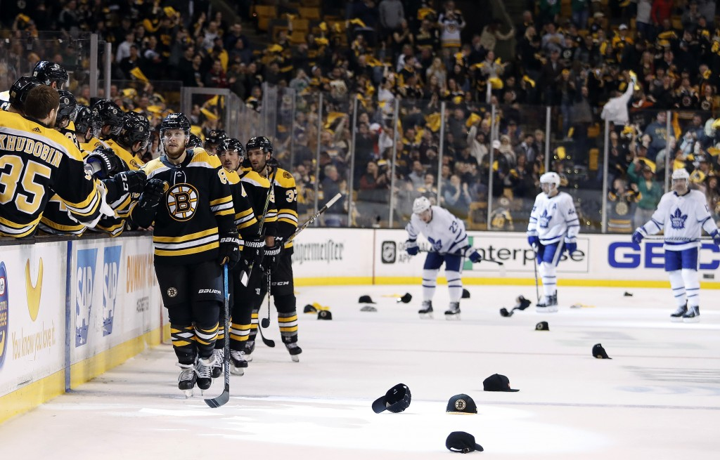 As hats litter the ice and Toronto Maple Leafs players head for the bench, Boston Bruins' David Pastrnak is congratulated at the bench after scoring h