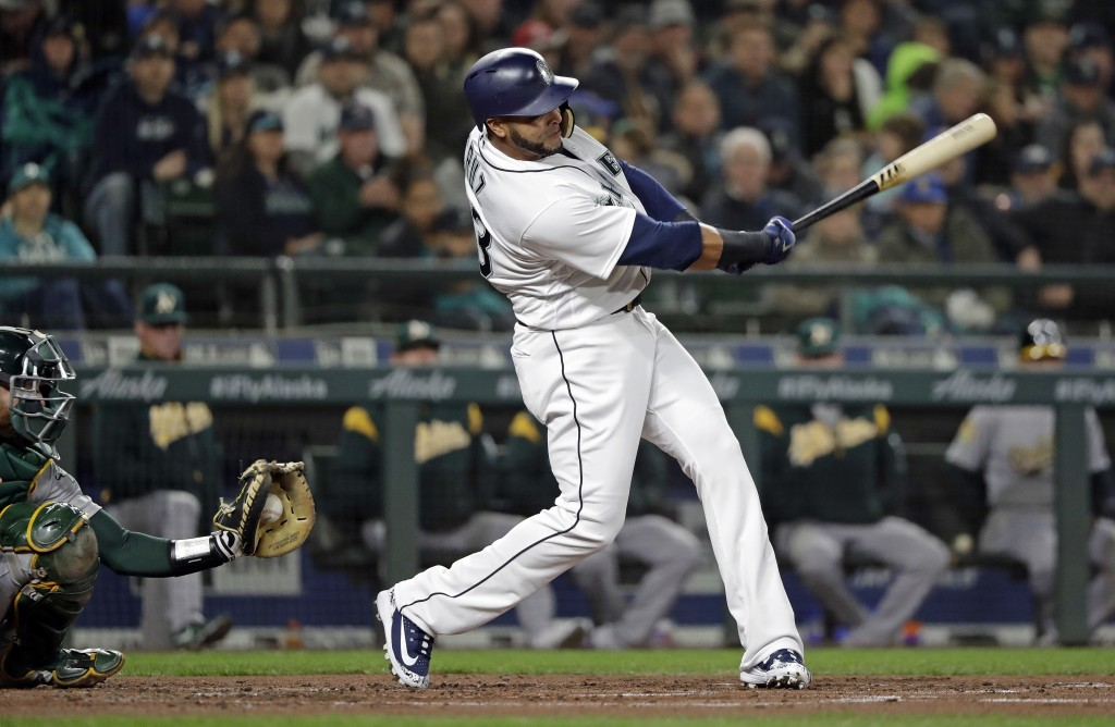 Seattle Mariners' Nelson Cruz, right, swings and misses to strike out as Oakland Athletics catcher Jonathan Lucroy catches the ball in the first innin...