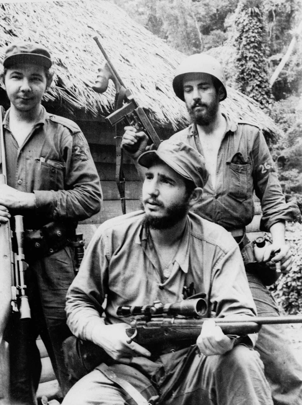 FILE - In this March 14, 1957 file photo, Fidel Castro, the young anti-Batista guerrilla leader, center, is seen with his brother Raul Castro, left, a