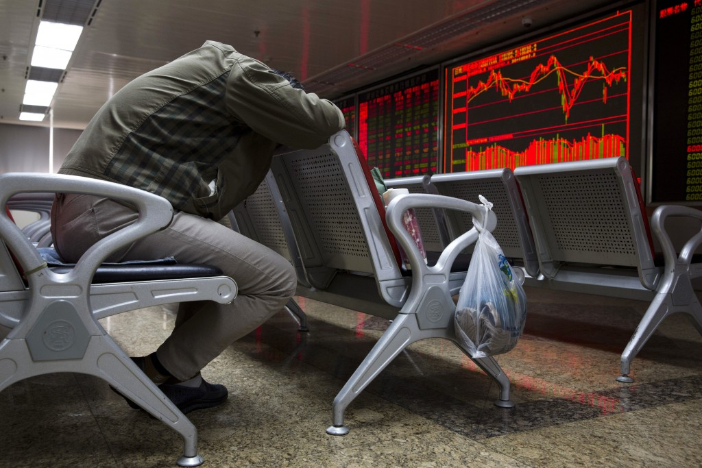 An investor rests near a display board for stock prices at a brokerage in Beijing Monday, April 16, 2018. Shares were mixed in Asia after an upbeat st